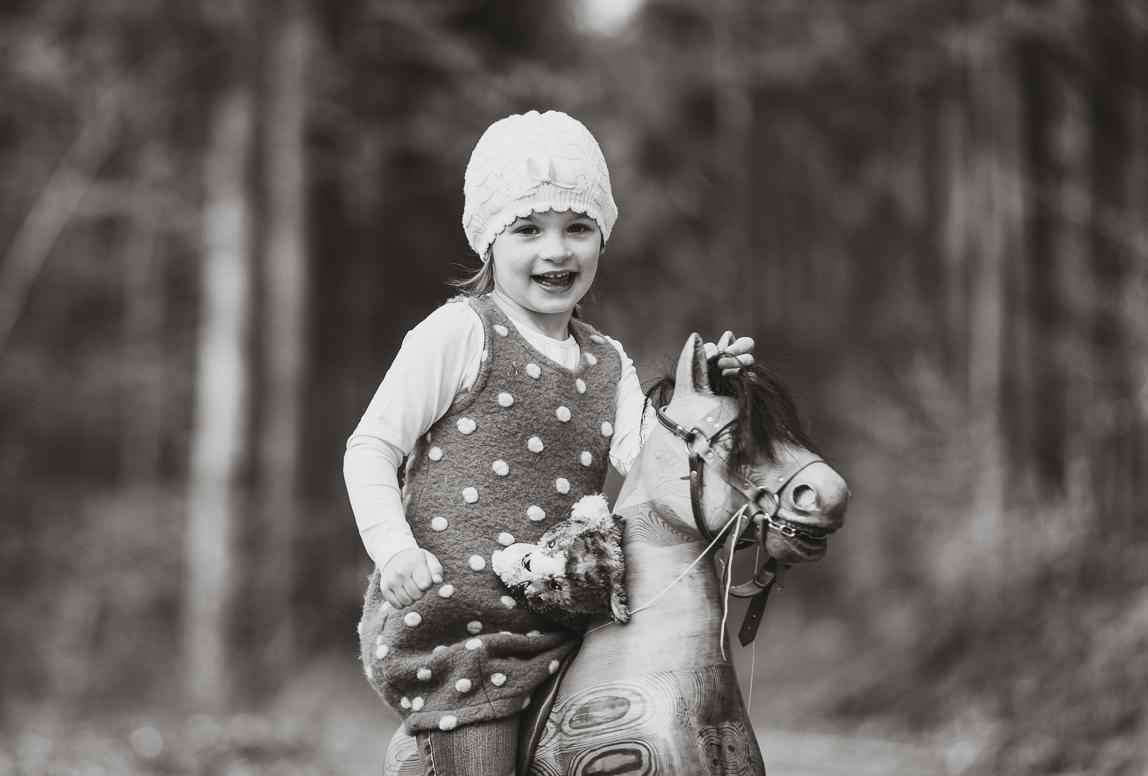 Kinderfotos Palma: Mädchen reitet auf Schaukelpferd