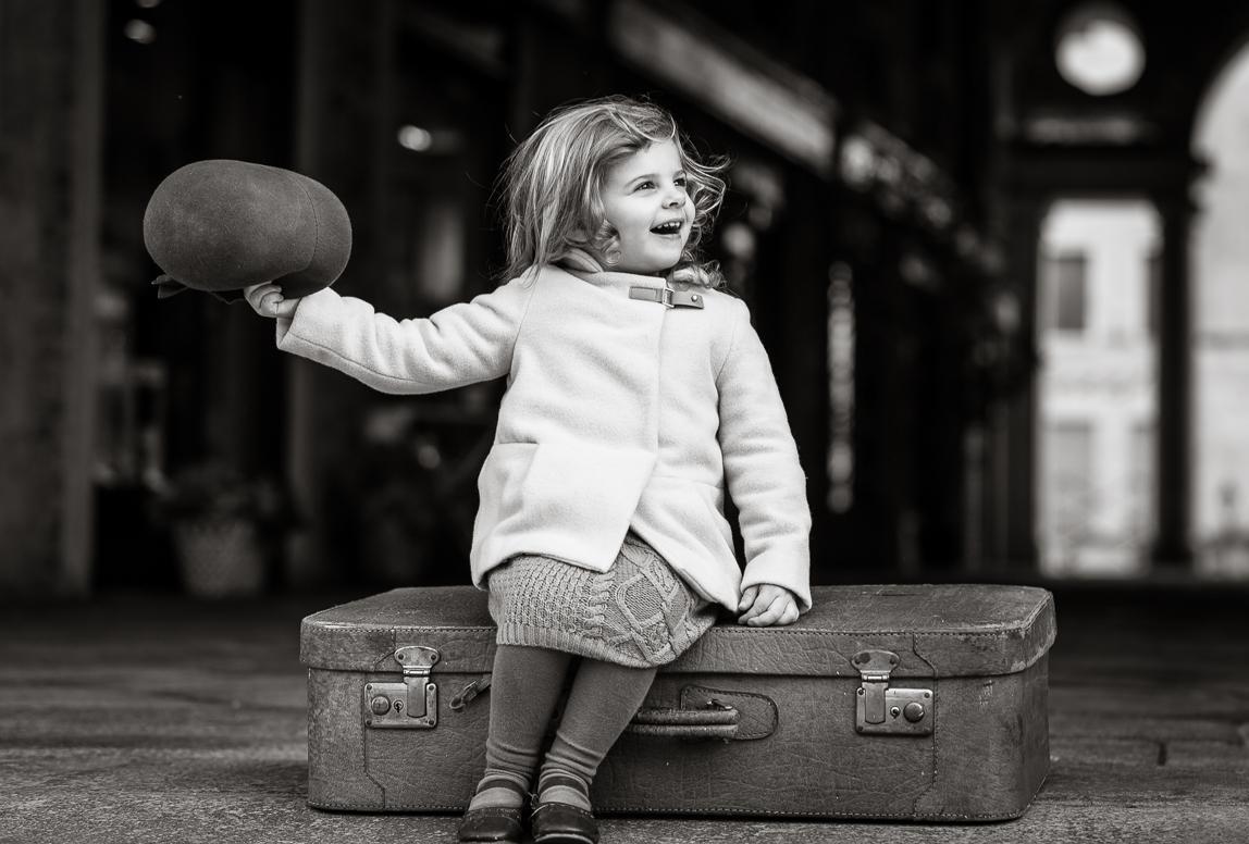 mallorca Kinderfotos: Junges Mädchen sitzt damenhaft auf Koffer in Palma