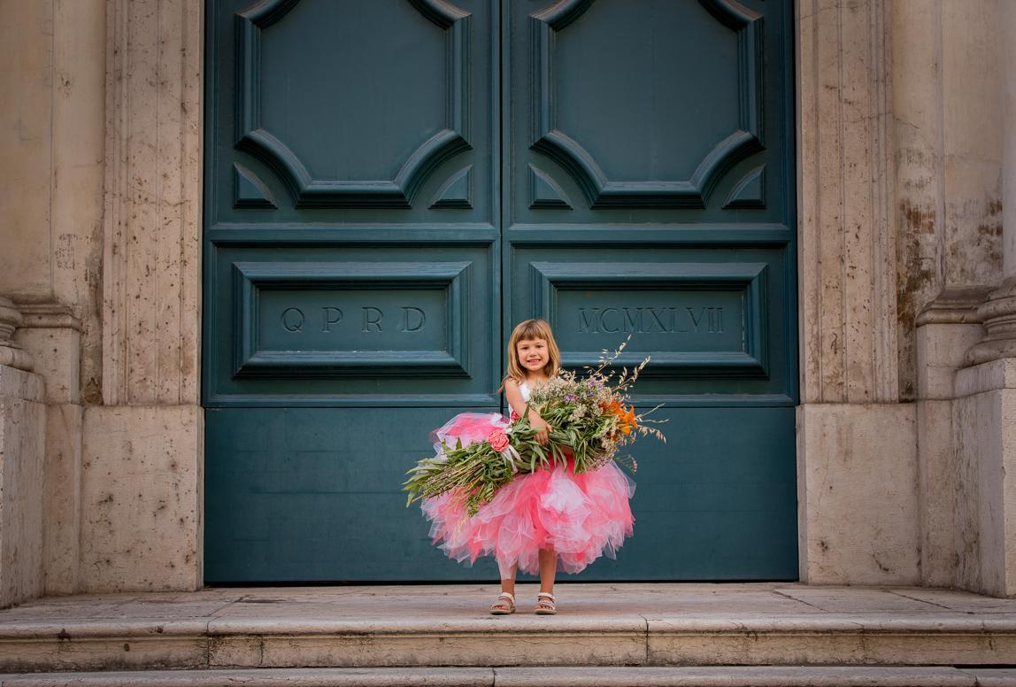Palma Kinderfotos: Mädchen mit riesigem Blumenstrauß vor alter Tür