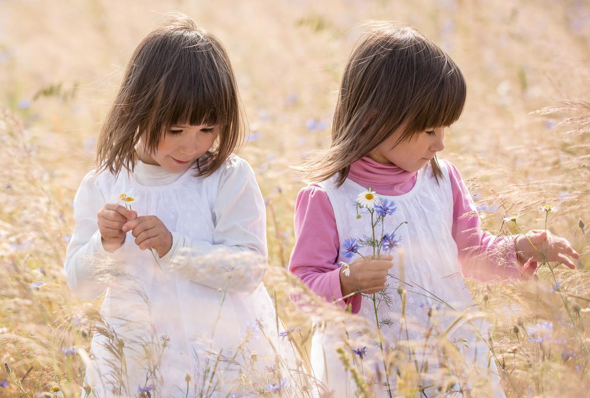 Alcudia Familienfotos: Zwillingsmädchen mit Blumen auf Feld