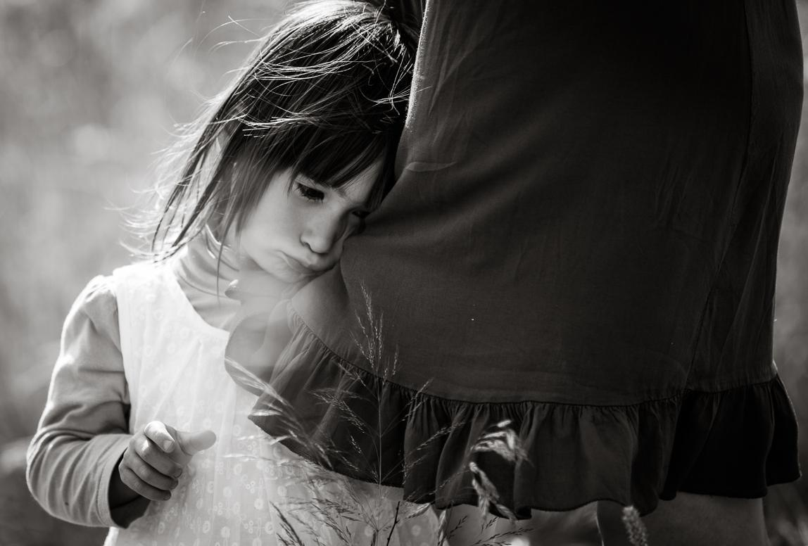 Familienfotos Majorca: Mädchen versteckt sich hinter der Mutter