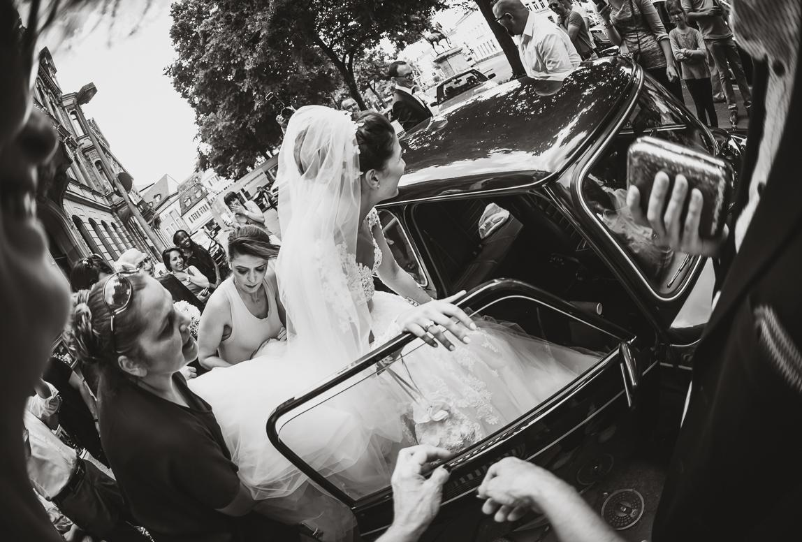 Hochzeitsfotografie Mallorca - Braut steigt unter Gästeschar ins Auto ein
