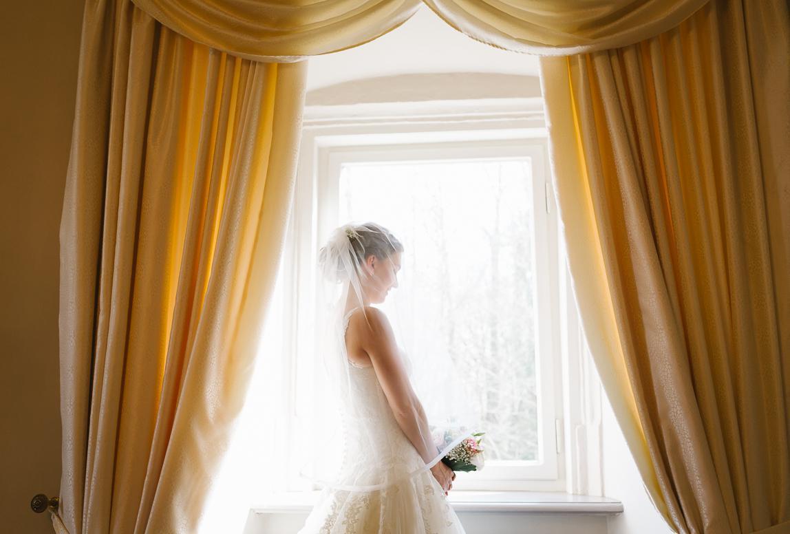 Hochzeitsphotographie Mallorca: Braut vor der Trauung im Gegenlicht am Fenster