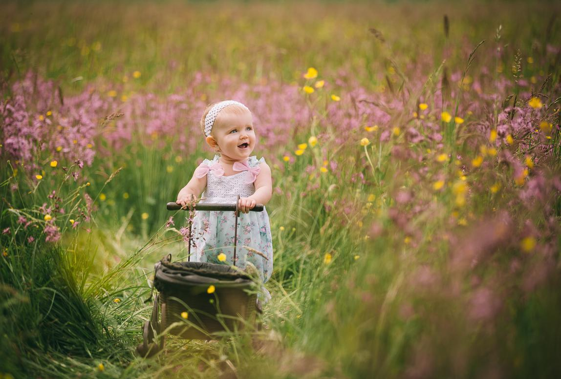 Mallorca Babyfotos: Baby mit Kinderwagen auf Wiese
