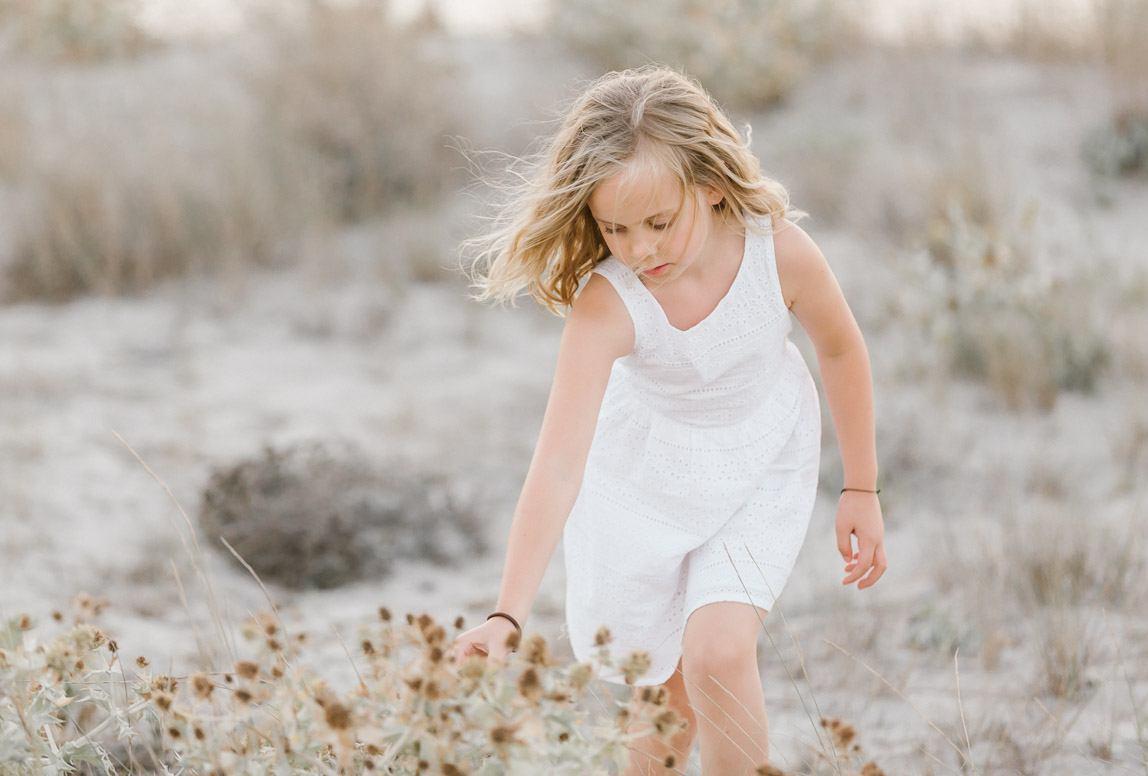 Mallorca Familienphotos: Mädchen pfückt trockene Blumen in Sanddünen