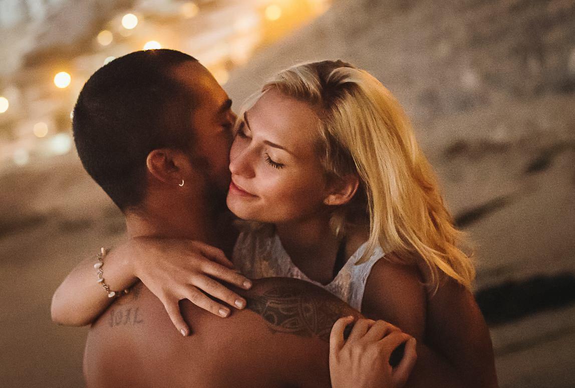 Paar Fotoshooting Palma - verliebtes Paar engumschlungen am Strand vor dem Hintergrund der Stadt