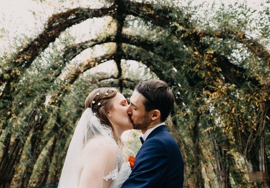 Mallorca Elopement Fotograf: Braut und Bräutigam küssen sich unter Weidenkirche
