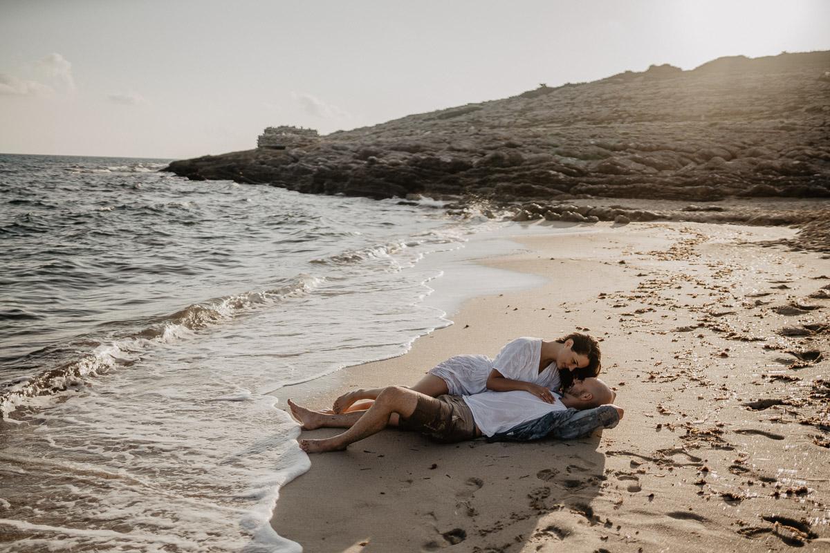 couple enjoying their mallorca honeymoon lying at the beach of cala mesquida during photo shoot with romany flower - best photographer in cala ratjada