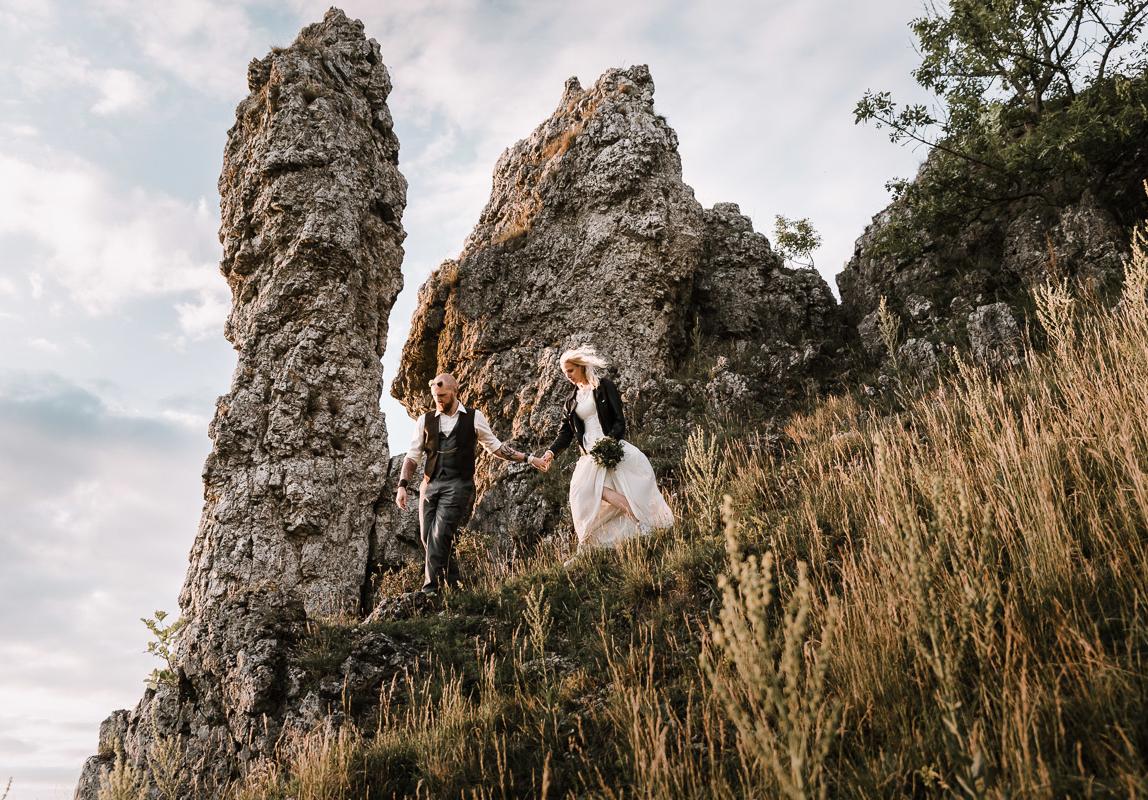 Coole Hochzeitsphotos Mallorca: Braut und Bräutigam auf Wanderung vor dramatischer Felslandschaft