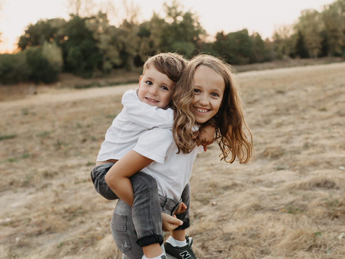 Familienfotos Cala Ratjada: Schwester trägt Bruder Huckepack