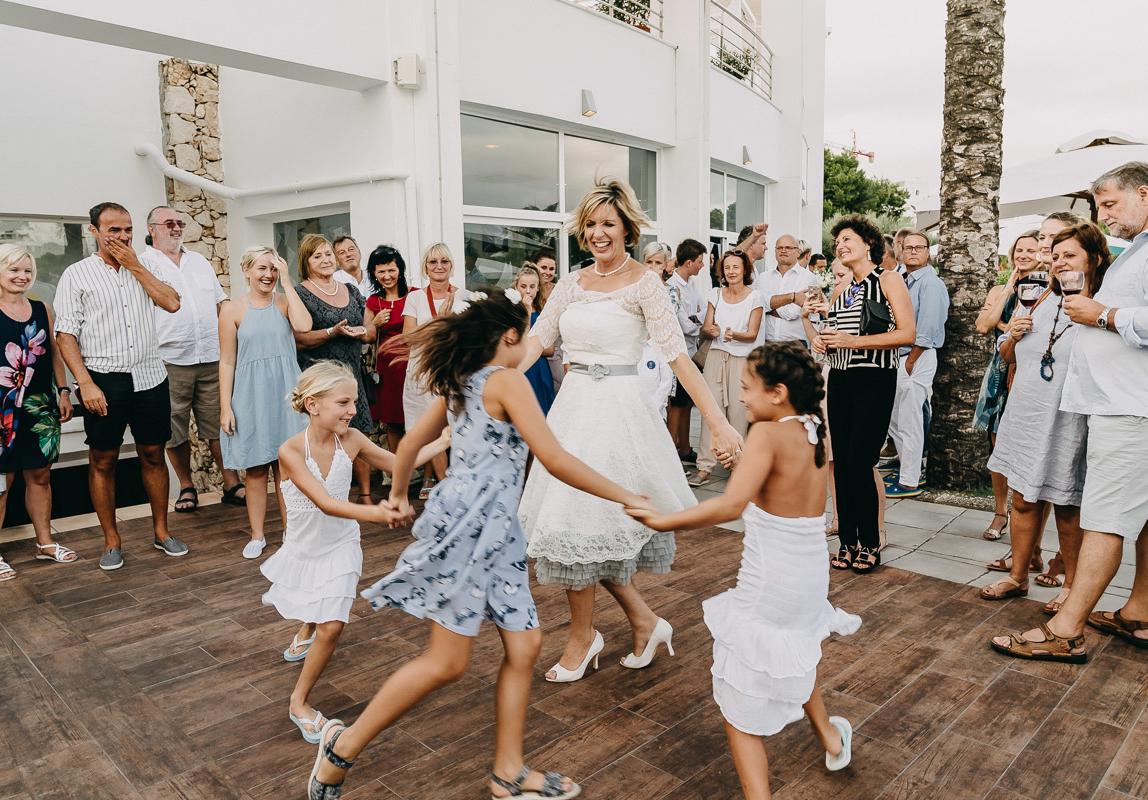Hochzeitsreportage Mallorca: Braut tanzt mit Kindern im Kreis bei Outdoor Hochzeit auf Mallorca